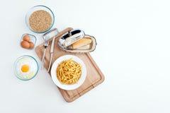 用手做的意大利tagliatelle面团 家做意粉 烹调意大利语的食品成分 面粉,鸡蛋,乳酪, -烹调在木sla的成份 库存照片