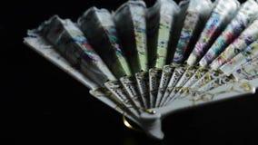 用手吹的冷空气中国折叠的爱好者在热在黑背景 股票视频