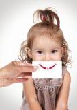 用手掩藏她的面孔的愉快的快乐的女婴与微笑和te 库存图片