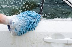 用手洗车 肥皂suds和洗涤的露指手套 免版税库存照片