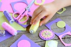 用手缝合概念的教的孩子 小孩子由毛毡圈子做了一朵花 儿童作为在手中穿线 库存图片