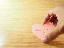 用手采取桃红色稠粘的纸笔记,告诉爱您 图库摄影