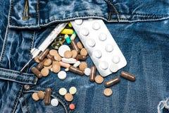 用拉锁拉上与五颜六色的药片和水银温度表作为泌尿生殖器的系统混乱的标志  药片或医学 免版税库存照片