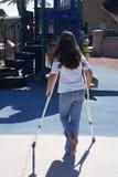 用拐杖支持女孩操场年轻人 库存图片