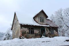 用新鲜的雪盖的小被毁坏的被放弃的房子 免版税库存照片