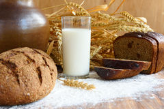 用早餐与一杯新鲜的牛奶和酥脆黑面包 免版税库存照片