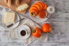 用早餐与柿子,瓶子在白色背景的果酱 库存照片
