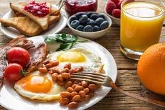 用早餐包括橙汁、煎蛋、烟肉、豆、果子和莓果 免版税库存图片