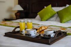 用早餐在一加上的床上咖啡和新月形面包 库存照片