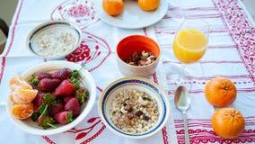用早餐在桌、汁液、谷物和果子上在阳光下 黏性物质 库存照片