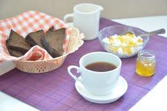 用早餐在桌杯子用茶,面包,凝乳在一块紫色餐巾的橙色果酱 库存照片