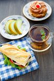 用早餐用三明治、茶、蛋糕和瓜 免版税库存图片