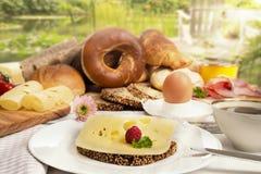 用早餐用乳酪面包、咖啡、鸡蛋、火腿和果酱在庭院里 图库摄影