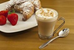 用早餐用咖啡、新鲜的新月形面包和草莓。 免版税库存图片