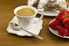 用早餐用咖啡、新鲜的新月形面包和草莓。 免版税图库摄影