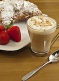 用早餐用咖啡、新鲜的新月形面包和草莓。 免版税库存照片