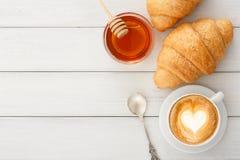用早餐用咖啡和新月形面包在白色土气桌上 库存照片