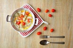 用早餐用在一个平底锅的煎蛋用白色猪肉香肠,蕃茄,在木背景的叉子 免版税库存照片