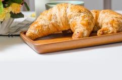 用早餐用在木板的新月形面包在白色背景中  免版税库存照片