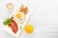 用早餐用在面包,烟肉,蘑菇,绿色的煎蛋 一杯咖啡和新鲜的汁液 图库摄影