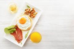 用早餐用在面包,烟肉,蘑菇,绿色的煎蛋 调味汁和新鲜的汁液 免版税库存图片