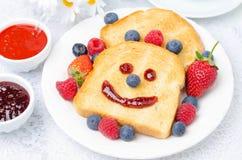 用早餐用微笑的多士,新鲜的莓果,果酱 免版税图库摄影