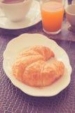 用早餐用新月形面包、咖啡和汁液- f的浅深度 免版税库存照片