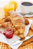 用早餐用新月形面包、果酱、咖啡和汁液 免版税库存照片
