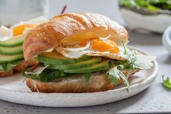 用早餐用新月形面包三明治用煎蛋、沙拉叶子和鲕梨 免版税库存照片