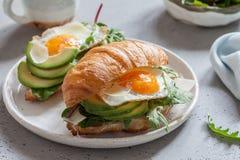 用早餐用新月形面包三明治用煎蛋、沙拉叶子和鲕梨 图库摄影