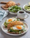 用早餐用新月形面包三明治用煎蛋、沙拉叶子和鲕梨 库存照片