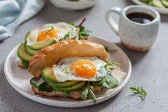 用早餐用新月形面包三明治用煎蛋、沙拉叶子和鲕梨 库存图片