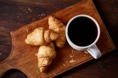 用早餐用新月形面包和无奶咖啡在木切板在土气背景,特写镜头,选择聚焦 免版税库存照片