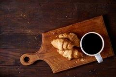 用早餐用新月形面包和无奶咖啡在木切板在土气背景,特写镜头,选择聚焦 免版税库存图片