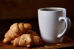 用早餐用新月形面包和无奶咖啡在木切板在土气背景,特写镜头,选择聚焦 免版税图库摄影