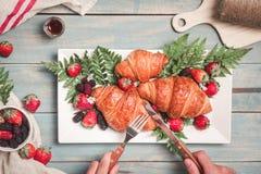 用早餐用新月形面包和草莓在蓝色木桌上 v 库存图片