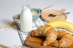 用早餐用新月形面包和Muesli和香蕉和新鲜的牛奶 免版税库存照片