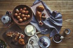 用早餐用新月形面包,无花果,在木板的咖啡在土气木背景,陶瓷盘,温暖的颜色,在看法上 免版税库存图片