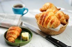 用早餐用新鲜的被烘烤的新月形面包、黄油和咖啡, newspa 免版税库存图片
