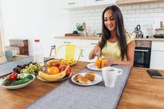 用早餐用果子、桔子、咖啡和新月形面包 厨房坐的表妇女 库存照片