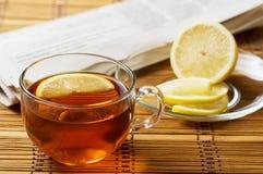 用早餐用柠檬和报纸在一张木席子 免版税库存图片