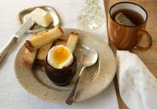 用早餐用煮沸的鸡蛋、油煎方型小面包片、黄油和茶 库存图片