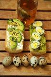 用早餐用茶和鲕梨三明治用鹌鹑蛋 免版税库存照片