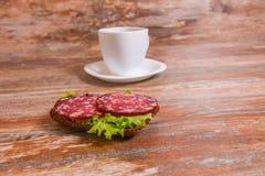 用早餐用蒜味咸腊肠三明治和茶 免版税图库摄影