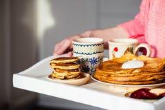 用早餐用薄煎饼、酸性稀奶油、果酱和热的饮料在盘子 免版税库存图片