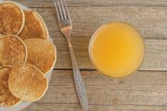 用早餐用薄煎饼和橙汁与金属叉子在一张木桌上 免版税库存图片