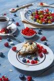 用早餐用被烘烤的豌豆和莓果在蓝色土气木头 免版税库存图片