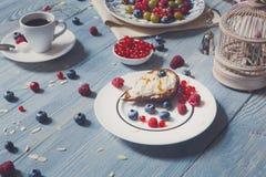 用早餐用被烘烤的豌豆和莓果在蓝色土气木头 图库摄影
