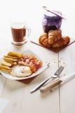 用早餐用鸡蛋、烟肉、炸薯条和咖啡 免版税库存照片