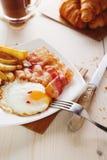 用早餐用鸡蛋、烟肉、炸薯条和咖啡 免版税库存图片